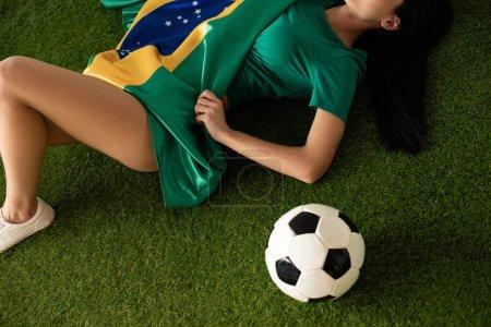 Photo pour Crochet vue d'une femme sexy couchée avec un ballon de football et un drapeau brésilien sur de l'herbe verte - image libre de droit