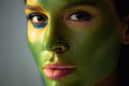 Photo for Attractive soccer fan with painted brazilian flag on face isolated on grey - Royalty Free Image