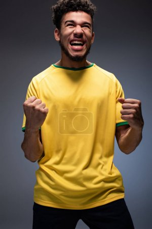 emotional african american football fan in yellow t-shirt shouting and gesturing on grey