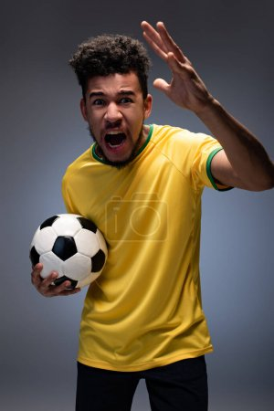 Photo for Aggressive african american football fan in yellow t-shirt shouting and holding ball on grey - Royalty Free Image