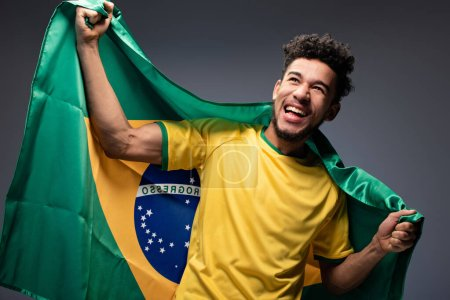 Photo for Happy african american football fan holding brazilian flag on grey - Royalty Free Image