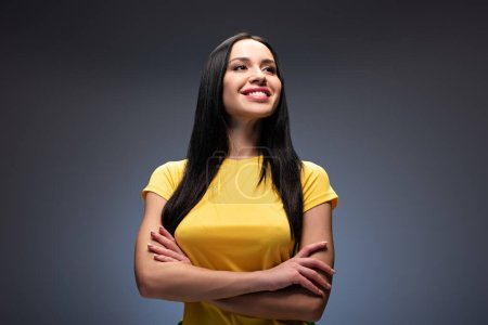 Photo for Proud smiling girl standing with crossed arms on grey - Royalty Free Image
