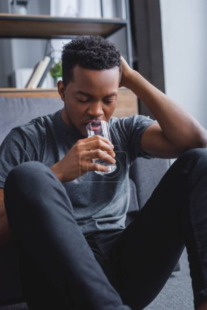 Photo for Stressed lonely african american man drinking water at home - Royalty Free Image