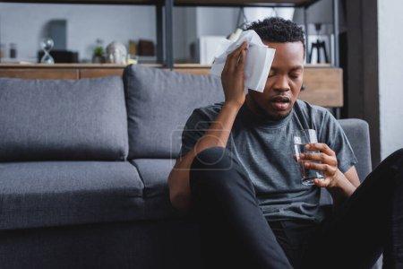Photo pour Homme afro-américain en sueur tenant un verre d'eau et des serviettes après une crise de panique à la maison - image libre de droit