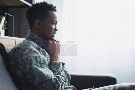 Photo for Emotional african american soldier in military uniform suffering from PTSD at home - Royalty Free Image