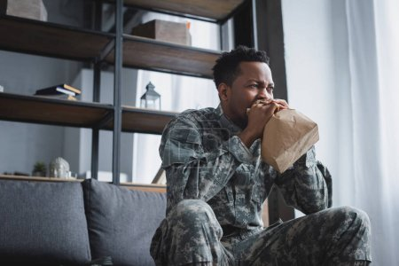 Photo for Stressed african american soldier in military uniform breathing with paper bag while having panic attack and suffering from PTSD at home - Royalty Free Image