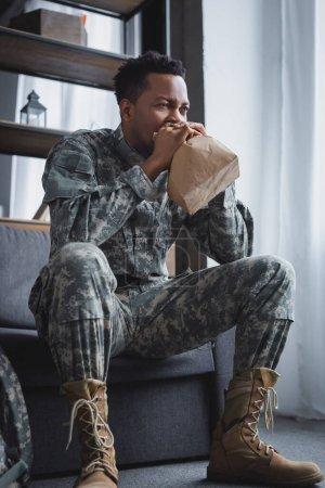 Foto de Soldado africoamericano en respiración uniforme militar con bolsas de papel mientras sufre un ataque de pánico en casa. - Imagen libre de derechos