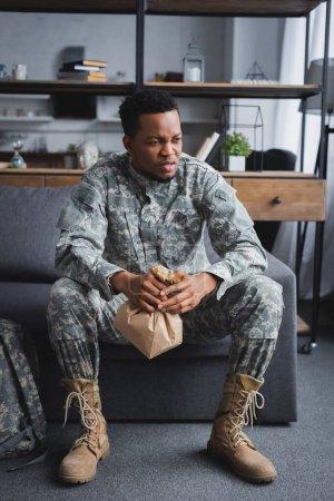 Foto de Soldado africoamericano en una bolsa de papel uniforme militar mientras sufren de ataques de pánico y de PTSD en casa. - Imagen libre de derechos