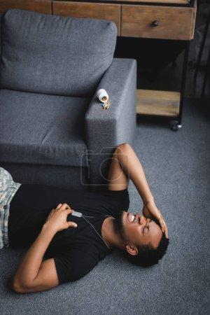 Foto de El soldado africoamericano estresado con una placa del ejército que tiene un ataque cardíaco en casa con pastillas, que sufre de PTSD. - Imagen libre de derechos