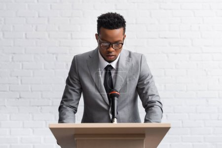 serious african american business speaker on tribune with microphone in conference hall