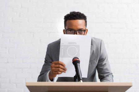 Photo pour Conférencier afro-américain nerveux caché derrière le papier lors d'une conférence d'affaires - image libre de droit