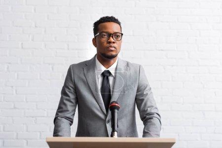 Photo pour Confiant homme d'affaires afro-américain ayant un discours sur tribune avec microphone dans la salle de conférence - image libre de droit