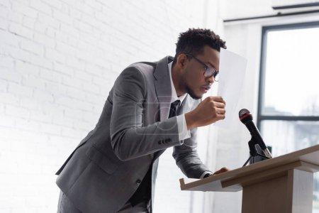 Photo pour Un orateur américain d'origine africaine se cache derrière le papier lors d'une conférence d'affaires - image libre de droit