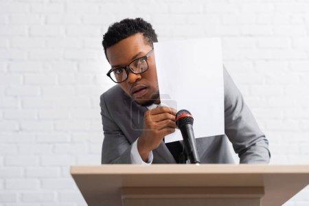 Photo pour Afro-américain effrayé orateur caché derrière le papier lors de la conférence d'affaires - image libre de droit