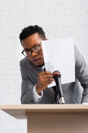 Photo for Frightened african american speaker hiding behind paper during business conference - Royalty Free Image