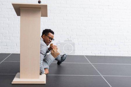 Photo pour Afro-américain effrayé haut-parleur avec sac en papier ayant crise de panique lors d'une conférence d'affaires au bureau - image libre de droit