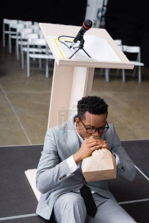 Photo pour Effrayé haut-parleur afro-américain respirant avec un sac en papier et ayant une crise de panique avant la conférence d'affaires - image libre de droit