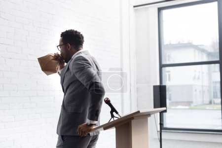 Photo for Nervous african american speaker breathing with paper bag and having panic attack during business conference in office - Royalty Free Image