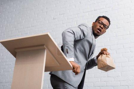 Photo pour Afro-américain effrayé haut-parleur tenant sac en papier et ayant une attaque de panique lors d'une conférence d'affaires au bureau - image libre de droit