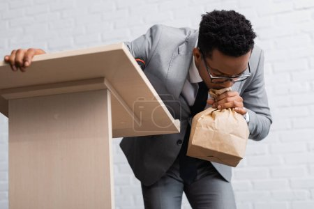 Photo for Nervous african american businessman breathing with paper bag and having panic attack during business conference in office - Royalty Free Image