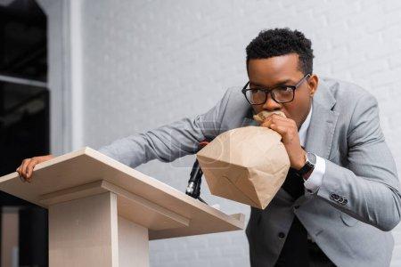 Photo pour Un orateur africain américain pressé respirer avec un sac en papier et avoir une attaque de panique sur une conférence d'affaires - image libre de droit