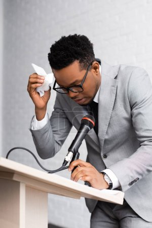 Photo for Nervous sweaty african american speaker with napkins and microphone on business conference in office - Royalty Free Image