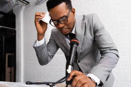 Photo pour Conférencier afro-américain en sueur frustré avec serviettes sur conférence d'affaires avec microphone - image libre de droit