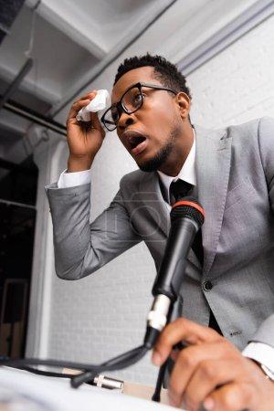 Photo pour Sueur nerveuse afro-américaine conférencier avec serviettes et microphone sur la conférence d'affaires au bureau - image libre de droit