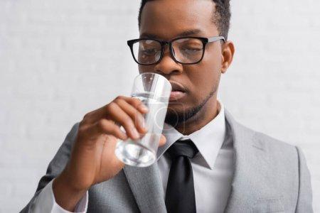 Photo pour Homme d'affaires afro-américain nerveux boire de l'eau sur la conférence d'affaires au bureau - image libre de droit