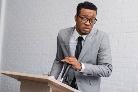Photo pour Frustré orateur african américain couvrant microphone lors d'une conférence d'affaires au bureau - image libre de droit