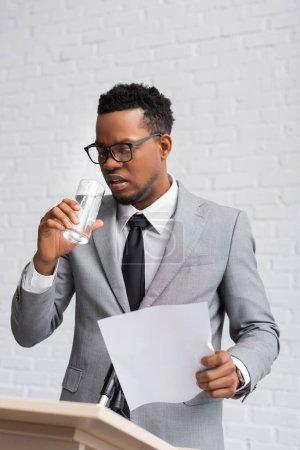 Photo pour Conférencier afro-américain nerveux tenant du papier et de l'eau potable lors d'une conférence d'affaires au bureau - image libre de droit