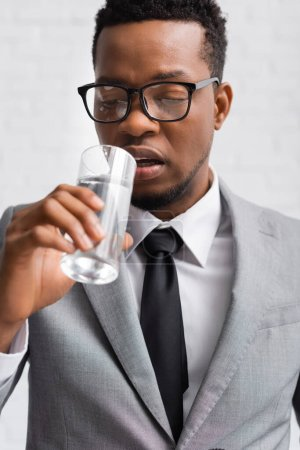 Photo for Nervous african american speaker drinking water on business conference in office - Royalty Free Image