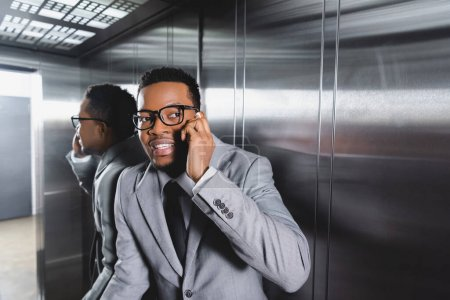 Photo for Stressed african american businessman talking on smartphone and suffering from panic attack in elevator - Royalty Free Image
