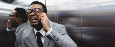 Photo for Panoramic shot of frightened crying african american businessman talking on smartphone and suffering from panic attack in elevator - Royalty Free Image