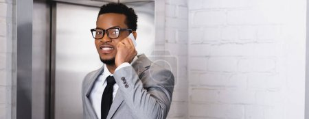 Photo for Panoramic shot of smiling african american businessman talking on smartphone while standing near elevator - Royalty Free Image
