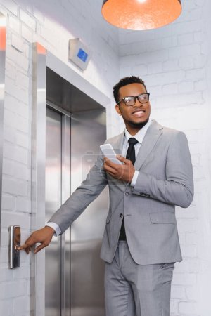 smiling african american businessman holding smartphone and pushing elevator button