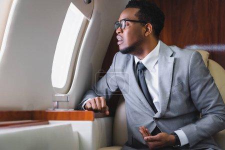 Photo pour Homme d'affaires afro-américain nerveux regardant par la fenêtre et ayant une attaque de panique pendant le vol en avion privé - image libre de droit