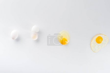 Photo for Top view of eggs transformation from raw to fried on white - Royalty Free Image