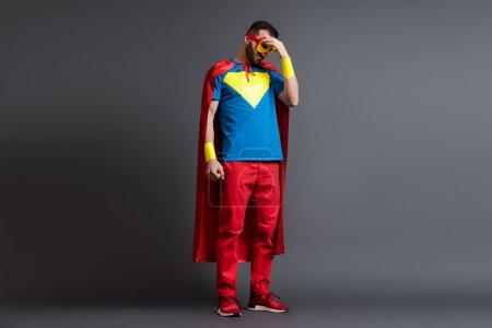 Photo pour Super héros fatigué en manteau et masque debout sur gris - image libre de droit