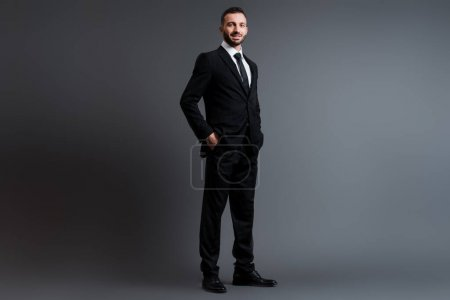 happy businessman in suit standing with hands in pockets on grey