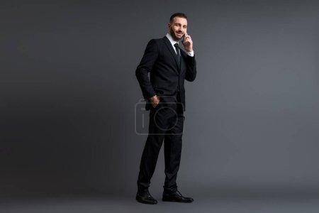 Photo pour Homme d'affaires joyeux en costume parlant sur smartphone tout en se tenant avec la main dans la poche sur gris - image libre de droit
