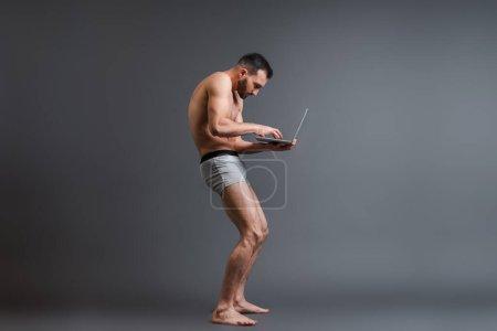 Photo pour Homme barbu et baissée en caleçon en utilisant un ordinateur portable sur gris - image libre de droit