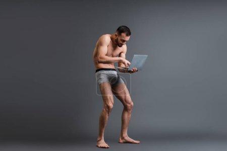 Photo pour Homme torse nu et penché en caleçon en utilisant un ordinateur portable sur gris - image libre de droit