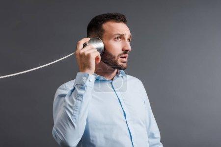 Photo pour Homme barbu tenant étain peut près de l'oreille tout en écoutant isolé sur gris - image libre de droit