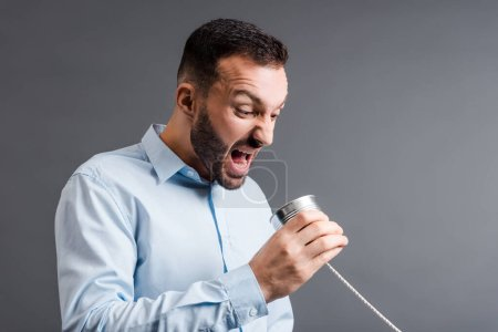 Photo for Angry man screaming while holding tin can isolated on grey - Royalty Free Image