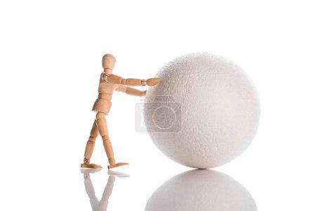 wooden doll near ball on white, evolution concept