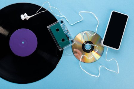 Photo pour Vue du dessus du disque vinyle vintage, disque compact, écouteurs, bande audio et smartphone avec écran blanc sur bleu, concept d'évolution - image libre de droit