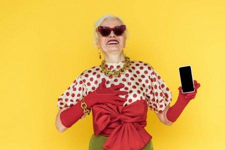Photo pour Femme âgée à la mode portant des lunettes de soleil souriant en tenant un téléphone intelligent isolé sur un téléphone jaune - image libre de droit