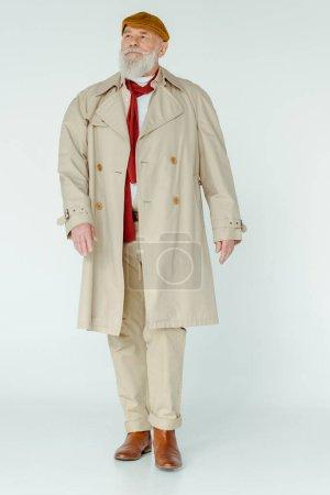 Volle Länge des stilvollen älteren Mannes im Trenchcoat, der auf weißem Hintergrund wegschaut