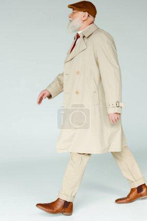 Photo pour Vue latérale d'un bel homme âgé en manteau marchant sur fond blanc - image libre de droit